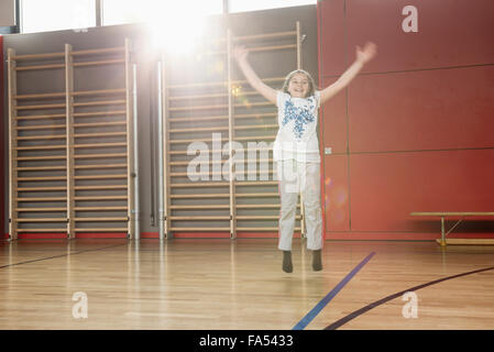 Cheerful small girl jumping in sports hall, Munich, Bavaria, Germany - Stock Photo