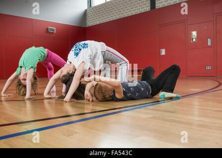 Girls doing bridge position yoga in sports hall, Munich, Bavaria, Germany - Stock Photo