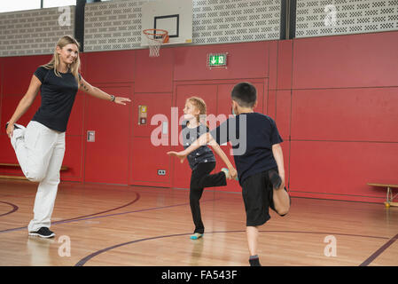 Teacher with children doing exercise in sports hall, Munich, Bavaria, Germany - Stock Photo