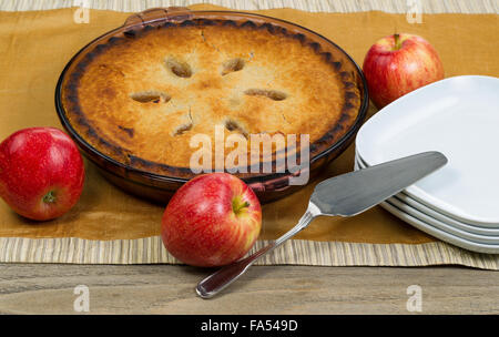 Freshly baked organic apple pie with whole apples, server and plates on brown table cloth. - Stock Photo