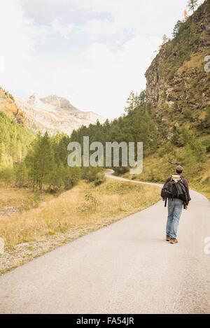 Rear view of a mature hiker walking on mountain road, Austrian Alps, Carinthia, Austria - Stock Photo