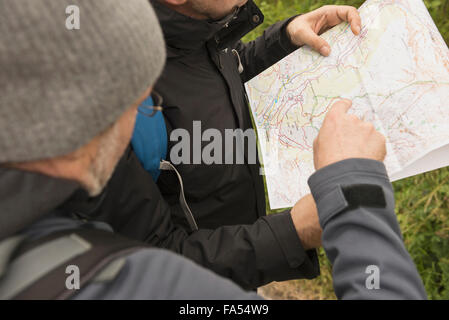 Two mature hikers checking the map for the right way, Austrian Alps, Carinthia, Austria - Stock Photo