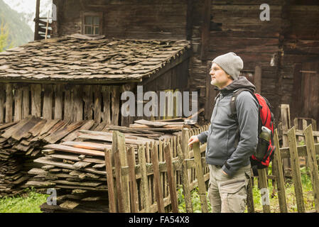 Mature hiker standing near cottage at rainy day, Austrian alps, Carinthia, Austria - Stock Photo