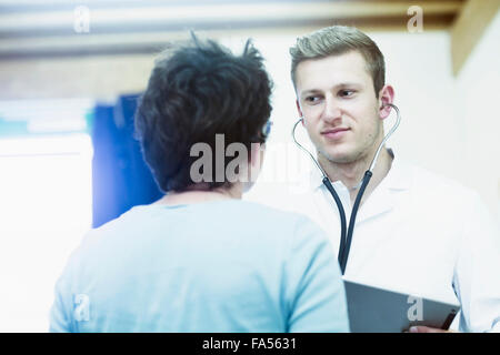 Mature patient talking to young doctor in a hospital, Freiburg Im Breisgau, Baden-Württemberg, Germany