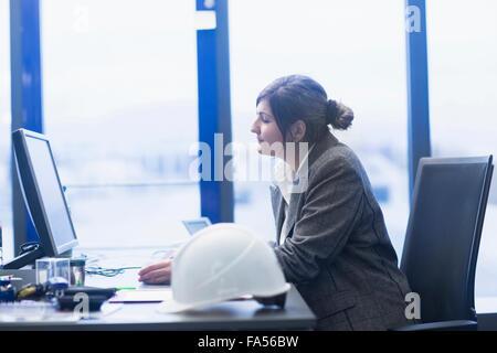 Businesswoman working on computer in office, Freiburg Im Breisgau, Baden-Württemberg, Germany - Stock Photo