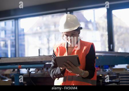 Female engineer using a digital tablet in an industrial plant, Freiburg Im Breisgau, Baden-Württemberg, Germany - Stock Photo