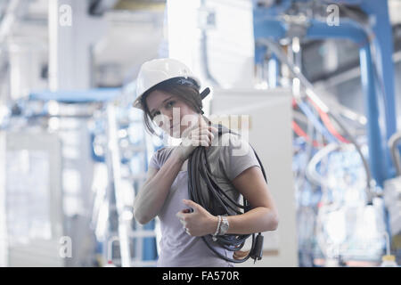 Female technician carrying coil of rope on shoulder in an industrial plant, Freiburg Im Breisgau, Baden-Württemberg, - Stock Photo