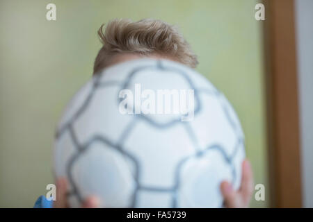 Boy holding football in front of his face, Freiburg im Breisgau, Baden-Württemberg, Germany - Stock Photo