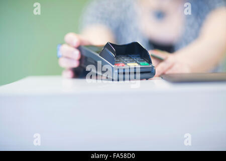 Close-up of credit card reader on checkout counter, Freiburg Im Breisgau, Baden-Württemberg, Germany - Stock Photo