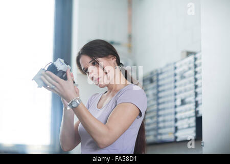 Female technician examining electrical component in an industrial plant, Freiburg Im Breisgau, Baden-Württemberg, - Stock Photo