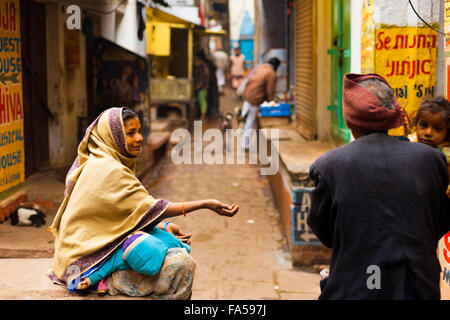 Poor woman sitting in dirty back alley holding baby begging for money from a passerby Stock Photo