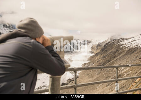 Mature man looking at view with telescope, Pasterze glacier, National Park Hohe Tauern, Carinthia, Austria - Stock Photo