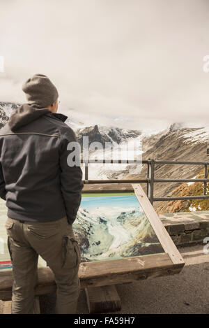 Mature man comparing the melting Grossglockner glacier and stream with a former image in a display cabinet, Carinthia, - Stock Photo
