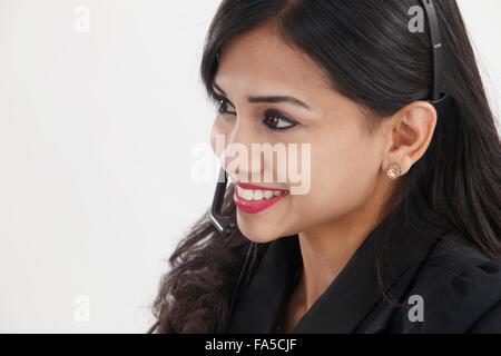 Side view of beautiful receptionist wearing head set talking - Stock Photo
