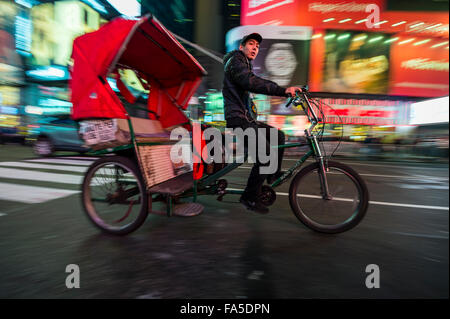 NEW YORK CITY, USA - DECEMBER 13, 2015: Passengers in the back of a pedicab look out as they pass through Times - Stock Photo