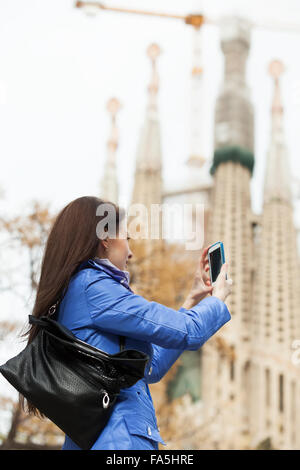 Woman with smartphone photographing herself against Sagrada Familia at Barcelona - Stock Photo
