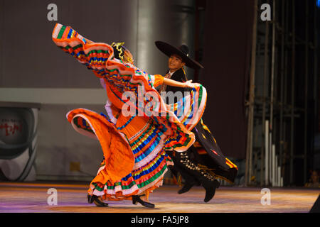 Female dancer in colorful orange dress repeatedly twisting and fluttering arms during a Mexican hat dance, traditional - Stock Photo