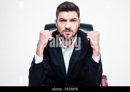 Angry annoyed bearded businessman in black jacket and white shirt sitting and showing fists over white background - Stock Photo