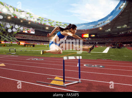 Track and field athletes in hurdle race - Stock Photo