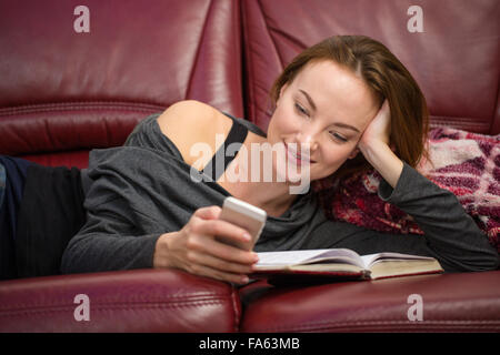 Smiling pretty young redhead woman reading book and using mobile phone at home - Stock Photo