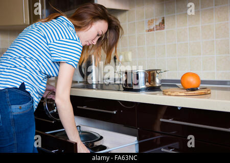 Concentrated pretty young woman taking pot and cooking on kitchen at home - Stock Photo