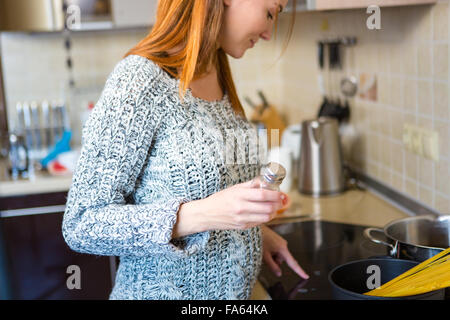 Charming pregnant redhead young woman in grey knitted sweater cooking italian spagetti in kitchen - Stock Photo