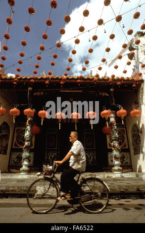 Man riding a bicycle in Chinatown of Melaka. Streets with red lanterns in the Chinatown district of Kampung Bakar - Stock Photo