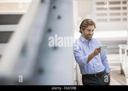 A man in shirt and tie using a smart phone in an urban scene. - Stock Photo