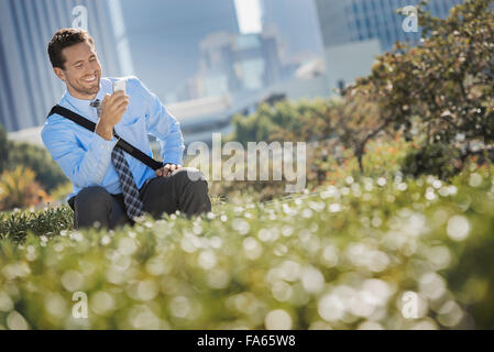 A young man on a park bench in the city, using a cell phone. - Stock Photo