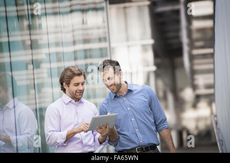 Two men standing outside a large building, one holding a digital tablet. - Stock Photo
