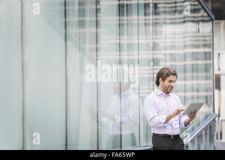 A man standing outside a building with large glass exterior panels, using a digital tablet. - Stock Photo