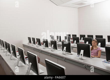 A school room, a computer lab with rows of screens and seating. A young person seated working at a terminal. - Stock Photo