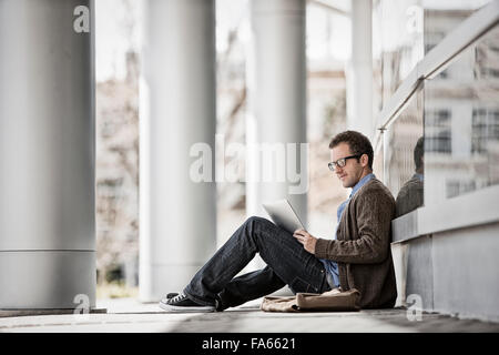 A man sitting outside a building on steps using a digital tablet. - Stock Photo