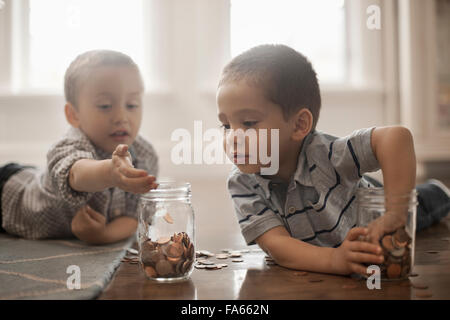 Two children playing with coins, dropping them into glass jars. - Stock Photo
