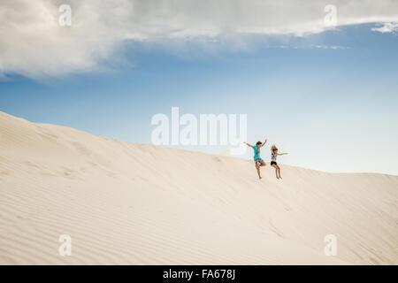 Boy and girl jumping in sand dunes, Green Head, Western Australia, Australia - Stock Photo