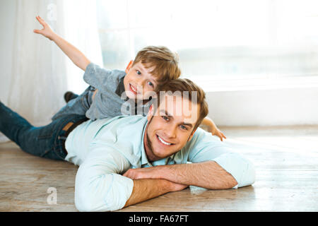 Little boy and his father on wooden floor - Stock Photo