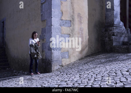 Woman standing in street text messaging, Lisbon, Portugal - Stock Photo