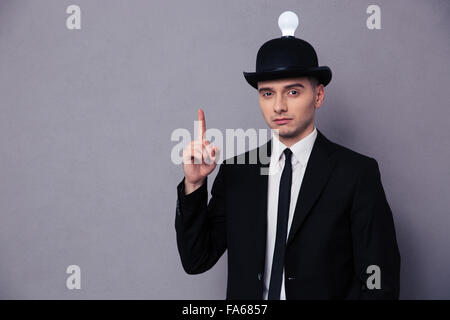 Portrait of a young businessman having idea over gray background - Stock Photo