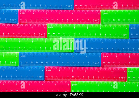 rows of colourful plastic blue pink and green rulers - Stock Photo