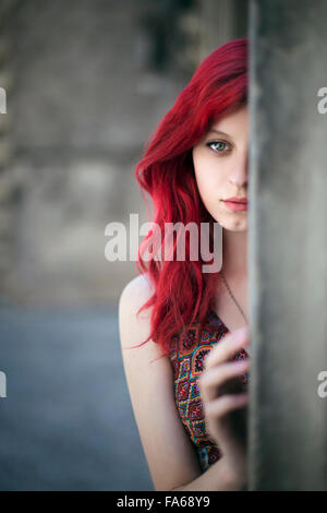 Teenage girl with red hair hiding behind a pillar - Stock Photo