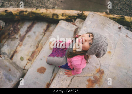 Elevated view of girl sitting on step wearing hat - Stock Photo