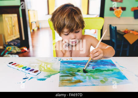 Boy painting with watercolours - Stock Photo