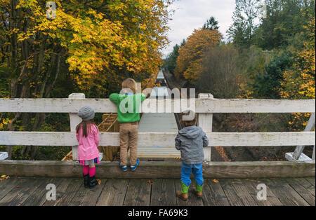 Three children standing on bridge watching train driving below - Stock Photo