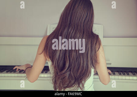 Rear view of girl playing the piano - Stock Photo