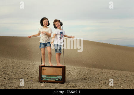 Boy and girl dancing on a old abandoned radio - Stock Photo