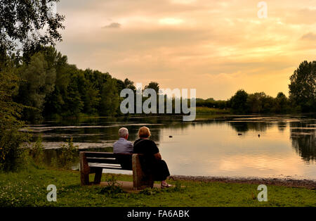 Mature couple sitting on bench overlooking lake with warm glow of evening, St Chad's Water off Wilne Rd, Derby Stock Photo