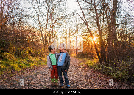 Two boys in the forest looking at each other and screaming - Stock Photo