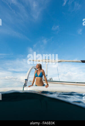 Woman getting out of the sea onto a boat, Bali, Indonesia - Stock Photo