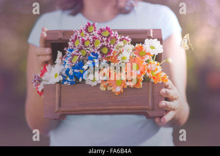 Butterfly flying next to a woman holding box of flowers