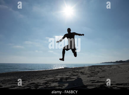 Silhouette of a man jumping in the air at the beach, Calabria, Italy - Stock Photo